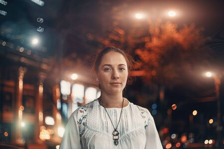 Portrait of young beautiful woman looks at camera on blurred illuminated street of night city background, toned Reklamní fotografie