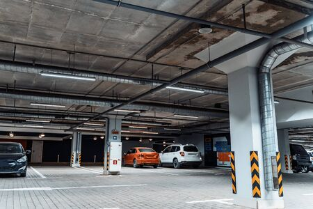 Illuminated underground car parking interior under modern mall with vehicles, toned