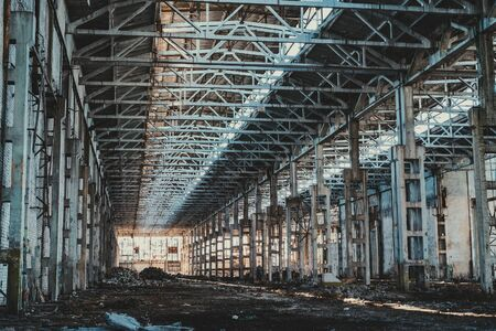 Ruined and abandoned industrial factory warehouse hangar with perspective view, toned Imagens