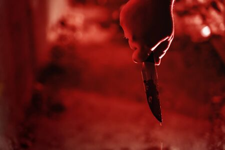 Male killer hand holding knife in blood in red illuminated dark scary house, toned Reklamní fotografie