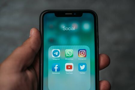 Moscow, Russia - Circa August 2019 : Iphone XR in male hand with icons of popular social media app or applications on screen for smartphone use lifestyle.
