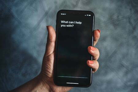 Moscow, Russia - Circa August 2019 : Siri - Apple voice assistant activated by voice in female hand and text on Iphone screen: What can I help you with? Voice mode of interaction with smartphone