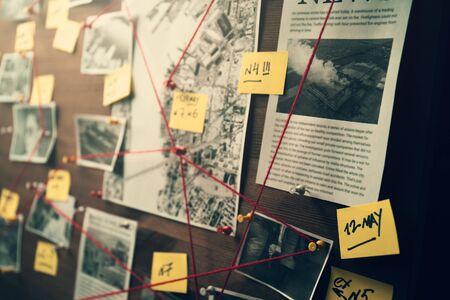 Detektivtafel mit Fotos von mutmaßlichen Kriminellen, Tatorten und Beweisen mit roten Fäden, selektiver Fokus, Retro-Ton