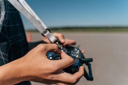 FPV drone remote controller in male pilot hands, close up