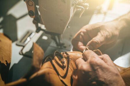 Working process of leather craftsman. Tanner or skinner sews leather on a special sewing machine, close up.