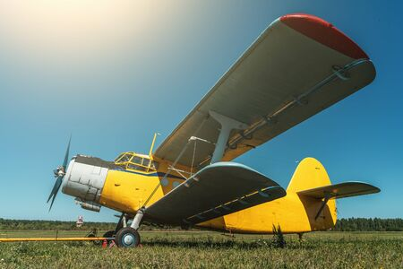 Vintage aircraft on green grass and blue sky background in sunlight. Old retro airplane.