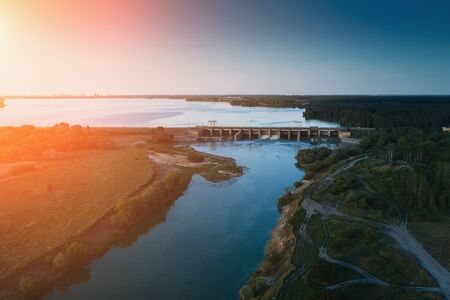 Aerial view of Dam at reservoir with flowing water at sunset, hydroelectricity power station, drone photo.