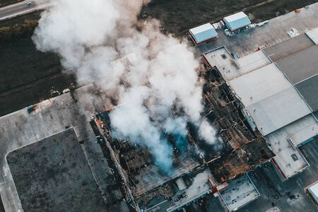 Aerial view of burning industrial building with huge smoke from burnt roof, fire disaster drone photo, toned