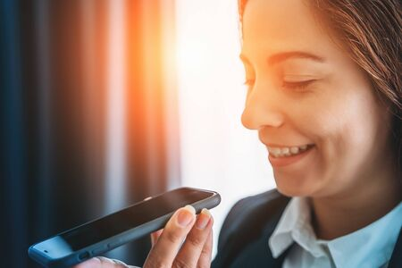 Young smiling business woman using vocal or voice activated digital assistant in smartphone, close up