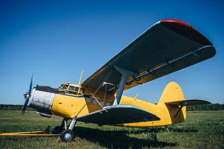 Vintage aircraft on green grass and blue sky background in sunlight. Old retro airplane. Фото со стока