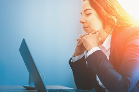 Young business woman looks at laptop in office, copy space, red and blue toned.