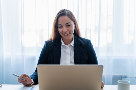 Young attractive caucasian woman smiling and making video call or online chat, looks at web camera of laptop. Distant teacher or coach, or tutor of online school or internet friend concept