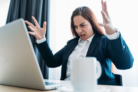 Stressed angry business woman screaming on laptop or notebook in office.