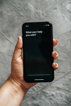 Moscow, Russia - Circa August 2019 : Siri - Apple voice digital assistant activated by voice in female hand and text on Iphone screen: What can I help you with?. Editorial