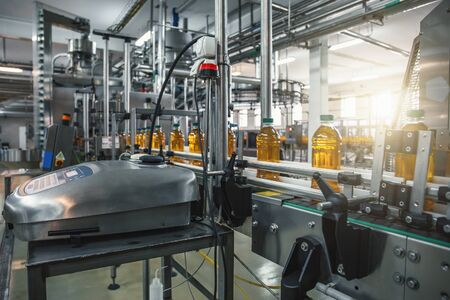 Conveyor belt, juice in bottles on beverage plant or factory interior in blue color, industrial production line, toned Фото со стока