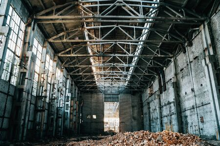 Ruined and abandoned industrial factory warehouse hangar with perspective view, toned Фото со стока