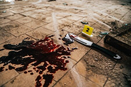 Crime scene with knife marked with number in blood of victim on floor. Investigation of cruel murder concept.