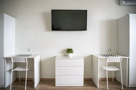 White room interior with TV on wall, two white tables and chairs, minimalist style.