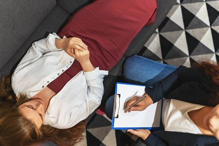 Psychologist listening to young depressed female patient lying on sofa and writing notes, top view, mental health and counseling concept