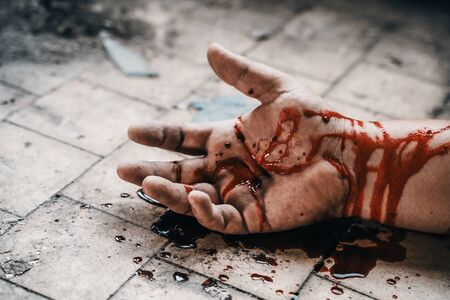 Crime scene with human hand in blood on floor of killed man by murder, dead body part close up