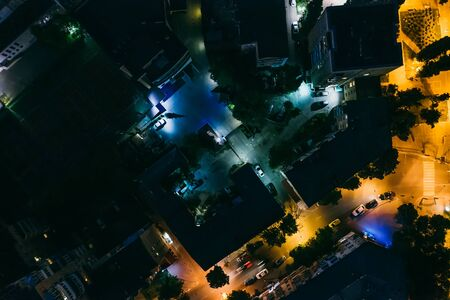 Aerial top down view of night city buildings and illuminated roads, drone photo.