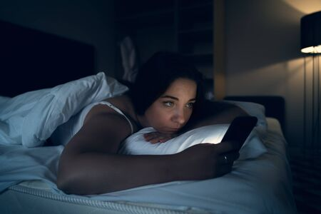Insomnia and social media addiction concept. Young woman uses smartphone while lying in bed at night, toned