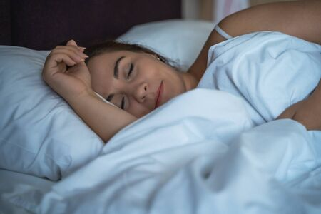Young beautiful girl or woman sleeping alone in big bed at night.
