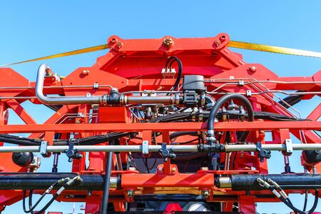Hydraulic system, steel tubes, industrial tools equipment on agricultural machinery tractor or harvester, close up.