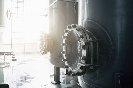 Iron or steel tank or cistern or reservoir for beverage with hatch in factory interior, toned Stock Photo