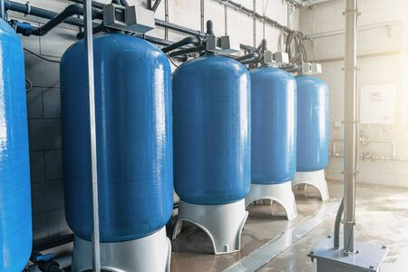 Purified drinking water factory or plant, large iron tanks and water purification filters and automation filtration system. Banco de Imagens