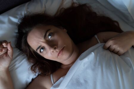 Depressed young woman dont sleep at night, lying on bed, looks up and suffers from insomnia, top view. Stock fotó