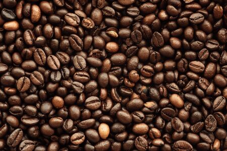 Fresh roasted brown coffee beans, top view of seeds texture as food background for design, macro photo. Фото со стока
