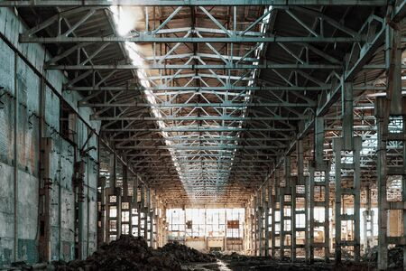 Ruined industrial hall of warehouse or hangar in process of reconstruction, toned