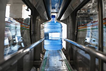 Water factory. Plastic bottle or gallon with pure water inside automated conveyor line machine.