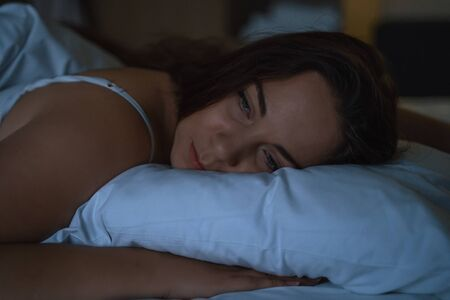 Young tired girl lies in bed, waking up at night, insomnia and overwork concept. Banque d'images - 130045888