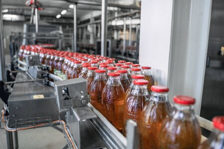 Conveyor belt or line in beverage factory or plant interior inside with modern industrial machine equipment. Bottles with fresh organic juice. Reklamní fotografie