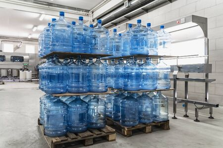 Water factory. Pallets with plastic bottle or gallon inside workshop interior.