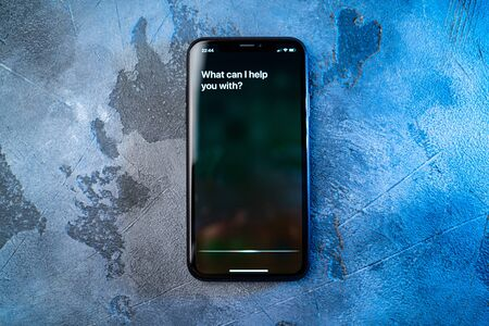 Moscow, Russia - Circa August 2019 : Iphone on concrete surface and activated by voice Apple digital assistant Siri and text on smartphone screen: What can I help you with?