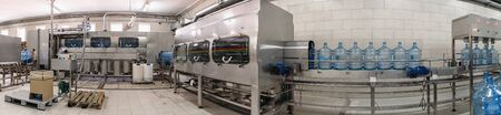 Panorama of conveyor line of plant for production of pure drinking water. Automatic conveyor equipment, flushing, disinfection and filling with water of reusable plastic bottles at factory.