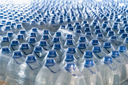 Many plastic bottles with drinking pure water and blue caps.