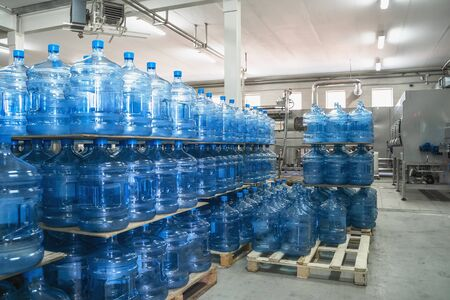 Gallons or plastic bottles of purified drinking water on pallets in factory interior inside.