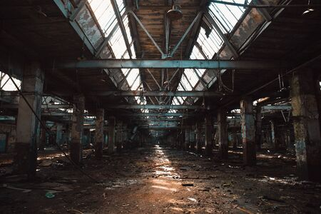 Ruined and abandoned industrial hall of warehouse or hangar in process of reconstruction, toned