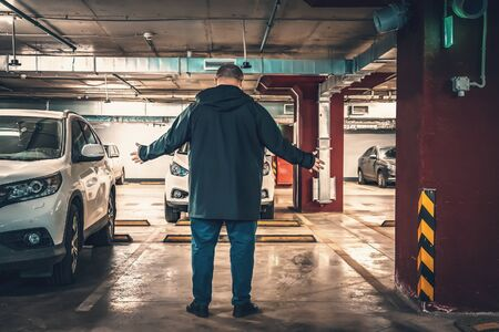 Astonished and surprised man discovered loss of car in underground garage parking lot. Stolen car concept, toned
