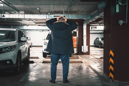 Stolen car concept. Surprised man discovered loss of car in underground garage parking lot, holding his head by hands.