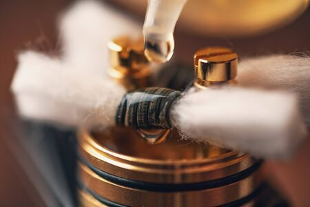 Rebuildable dripping atomizer or RDA for vaping or e-cigarette with coil and cotton stripes wetted with e-liquid, macro photo with selective focus Stock Photo