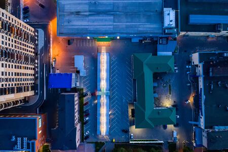Top down view of night city buildings, yards and streets, aerial shot, toned