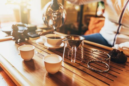 Chinese tea ceremony, girl makes boiling water from a teapot black tea puer in taiwan on wooden teatable in sunlight, selective focus.