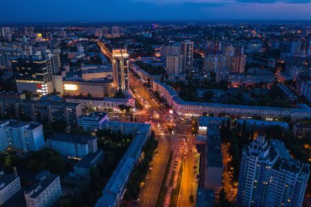 Aerial view of night city with illuminated roads, car traffic and different buildings, drone shot. Stock Photo