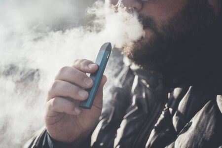 Man smokes new Vape Pod System, inhales and exhales vapor of electronic cigarette, vaping concept, selective focus, toned Stock Photo