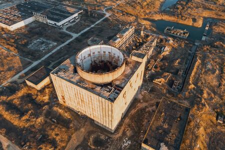 Aerial view from drone of abandoned and ruined Nuclear Power Plant or station, round tower of atomic reactor, large industrial demolished building, toned Stock Photo